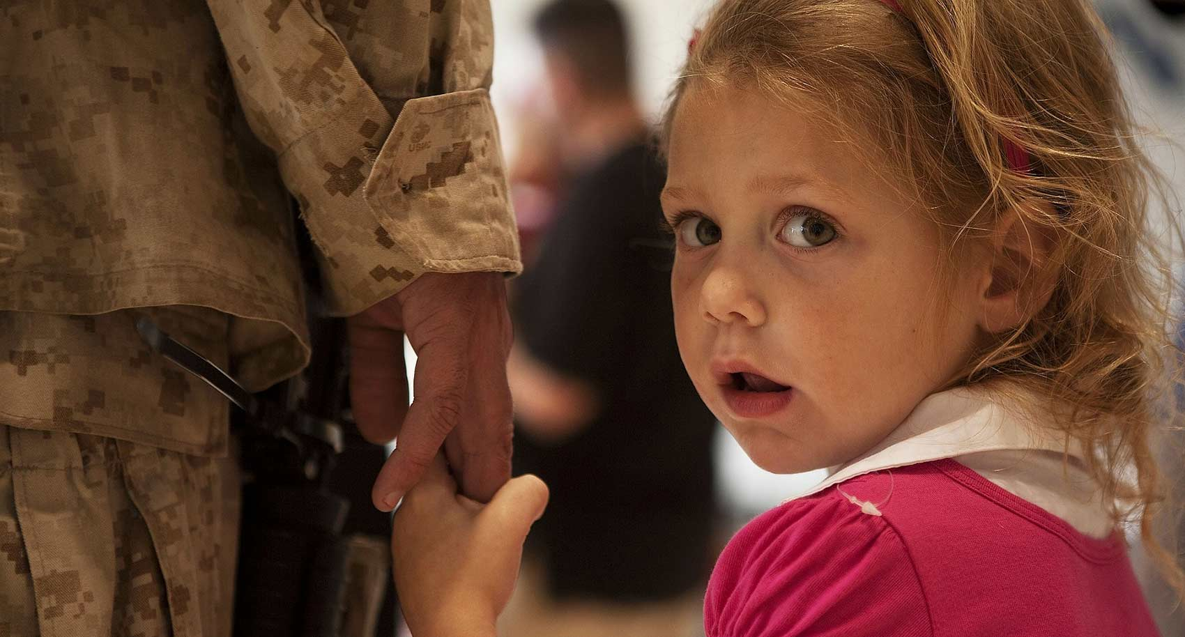 Girl holding soldiers hand